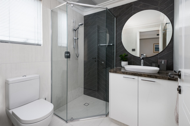 frameless-shower-black-tiles-chevron-round-mirror