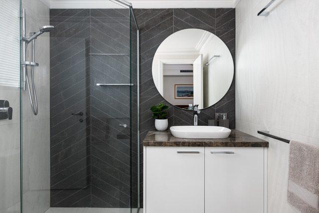 frameless-shower-black-tiles-round-mirror-single-vanity
