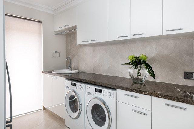 laundry-washer-dryer-white-cabinets-granite-benchtop