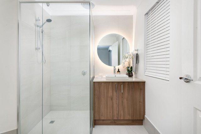 backlit-circle-mirror-frameless-shower-basin